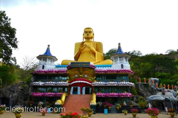 Buddha's golden statue sitting on top of museum seen from the main road.